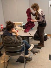 Jodi Movins has a pair of pants hemmed by volunteer Patti Villiere.