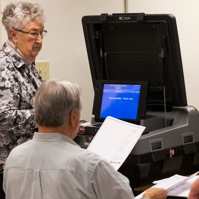 Ballots are fed into a machine at the Rock County Courthouse