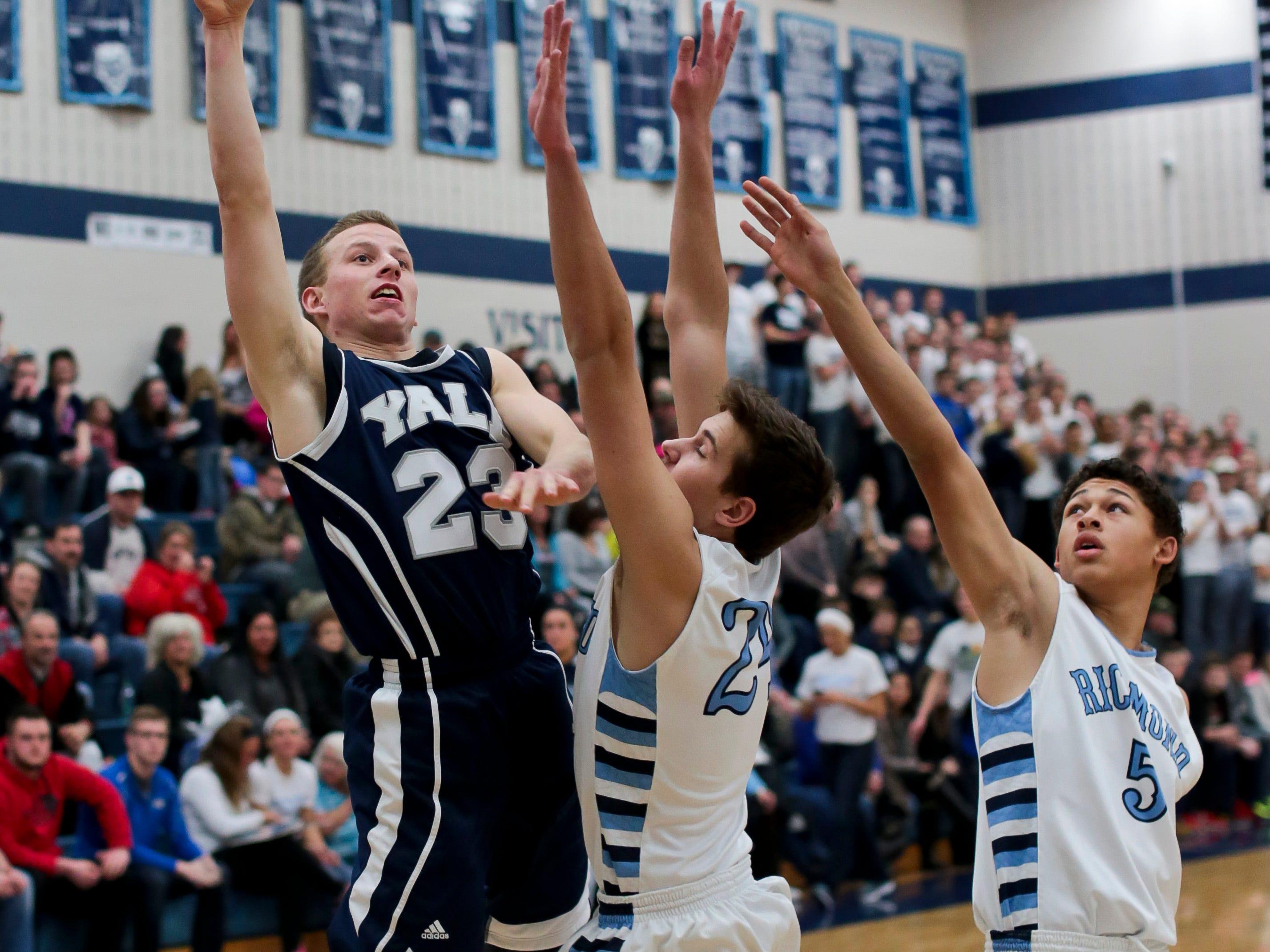 Yale senior Josh McClelland takes a shot over Richmond senior Evan Kratt and sophomore D'Sean Hamilton during a basketball game Friday, Feb. 27, 2015 at Richmond High School.
