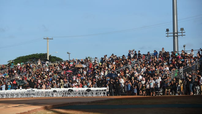 In this May 22, 2016, file photo, attendees in the bleachers at Paseo stadium stand for the National Anthem and Guam Hymn during the 12th Festival of Pacific Arts Guam 2016 opening ceremony.