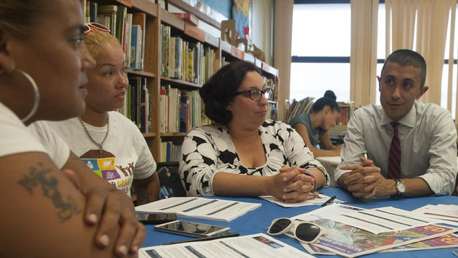 Superintendent Paymon Rouhanifard, right, talks to Camden parents, from left, Vanesa Cerrano, left, Janeti DeJesus and Isy Payamps during a Camden School Town Meeting at the Cooper's Poynt School in Camden.