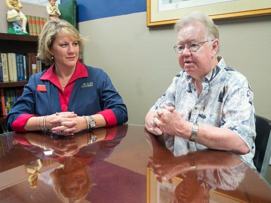 Assistant administrator Kace Browning, left, listens