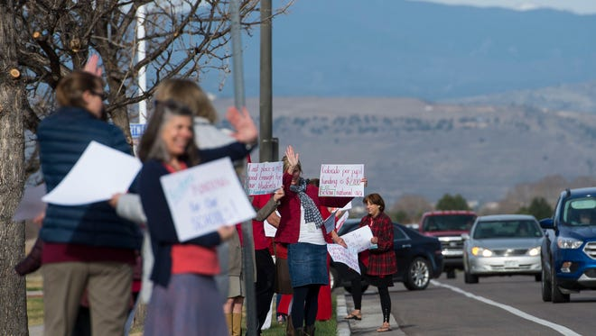 "Elementary school employees wave to passing traffic while holding signs during a ""walk-in"" on Monday morning, April 16, 2018, outside of Traut Core Elementary School in Fort Collins, Colo."