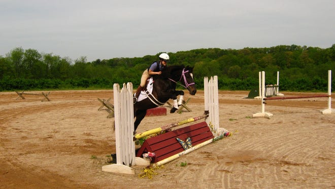 Nicole Wiley, co-founder of Ride to Survive, is shown jumping her horse, Bella. On Oct.. 15, Ride to Survive will hold a horse show in support of survivors of violence.