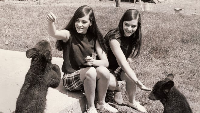 Bear cubs get treats from the Twin Tiers Twins, Candy and Cindy Doty, in this undated photo.