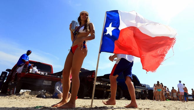 Beach goers walk past a Texas flag planted on the ground during spring break Monday, March 14, 2016, in Port Aransas.