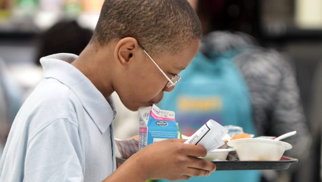 Elijah Busch, a fifth at Rockdale Academy, Avondale,  finishes off his milk as he walks across the   school cafeteria to return his tray at the end of the lunch period.  The Enquirer/Patrick Reddy