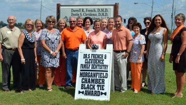 Drs. French & Clevidence  Family Dentistry received the Morganfield Chamber of Commerce's Black Tie Award following the September 8 chamber meeting.  Pictured in the middle are Dr. Darrell French; Dr. Brittany French Clevidence; and Dr. Dustin Clevidence.  They are  surround by their office staff and chamber members. The award is presented monthly to a local business that maintains an attractive store front.