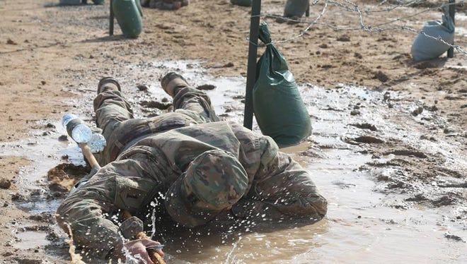 Troopers from the 2nd Squadron, 13th Cavalry Regiment crawl through mud during their Spur Ride in Kuwait.