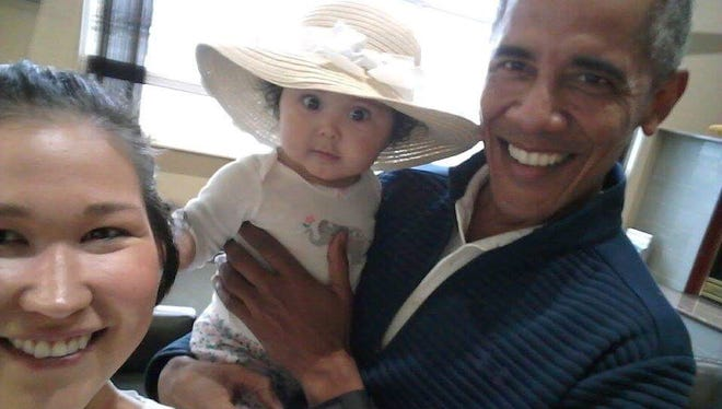 """In this July 3, 2017 photo provided by Jolene Jackinsky, former U.S. President Barack Obama holds Jackinsky's 6-month-old baby girl while posing for a selfie with the pair at a waiting area at Anchorage International Airport, in Anchorage, Alaska. Jackinsky said Obama walked up to her and asked, """"Who is this pretty girl?"""""""