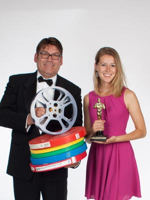 Tom Crane and Kelly Fitzgerald are pictured holding film reels. Kelly, a college undergraduate, handled communication fo Tom this summer prior to leaving to study abroad in London.