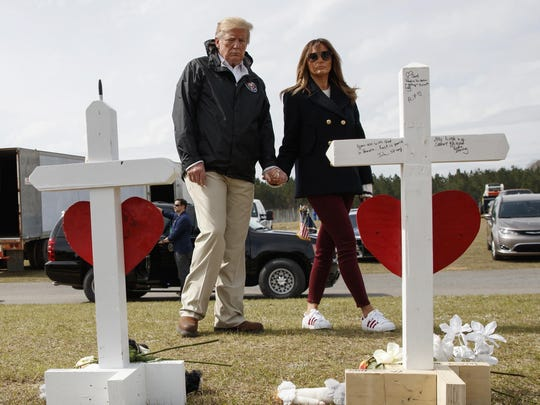 In this March 8, 2019 photo, President Donald Trump and first lady Melania Trump visit a line of crosses at Providence Baptist Church in Smiths Station, Ala., as they tour areas where tornados killed 23 people in Lee County, Ala. Trump has had it with the #fakeMelania conspiracy theories circulating on social media. Trump is claiming that photos of his wife were altered to make it appear that a look-alike accompanied him to Alabama last week.