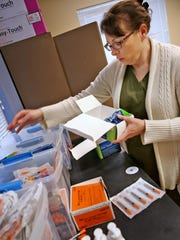Public health nurse Brittany Combs restocks needles March 24,2016, at a needle-exchange program in Austin, Ind.