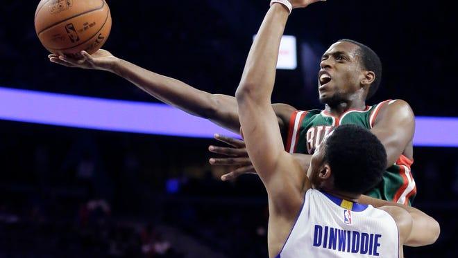 Milwaukee Bucks guard Khris Middleton, top, goes to the basket against the Detroit Pistons' Spencer Dinwiddie on Nov. 28, 2014, in Auburn Hills.