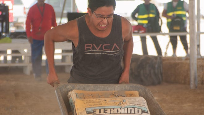 Joshua Paytiamo, 21, heaves a wheelbarrow carrying bags of concrete in the Northern Navajo Nation Fair's first endurance contest on Friday in Shiprock.