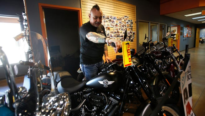 Harley-Davidson salesman Jim Johnson shows off a model Wednesday at Four Corners Harley-Davidson in Farmington. The motorcycle is one of five being raffled off Saturday during a fundraising event at the Aztec Speedway.