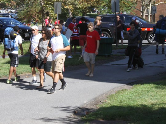 A new student walks with his family during move-in