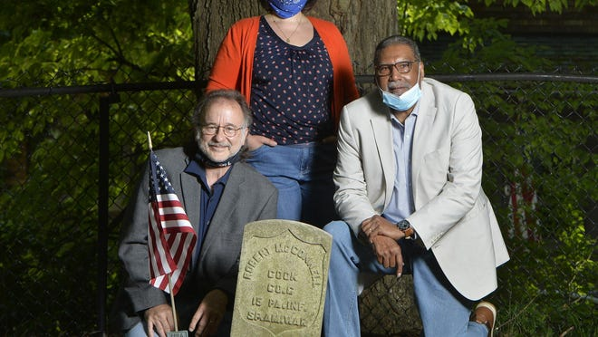 From left, Chris Magoc, Mercyhurst University history professor; Melinda Meyer, chair of Preservation Erie, and historian Johnny Johnson gather at the grave of Robert McConnell in the Gospel Hill Cemetery on Thursday in Harborcreek Township. McConnell was the son of a freed slave and served in the Spanish-American War.