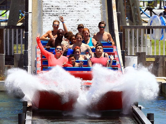 Patrons raises their hands as they prepare for a splash