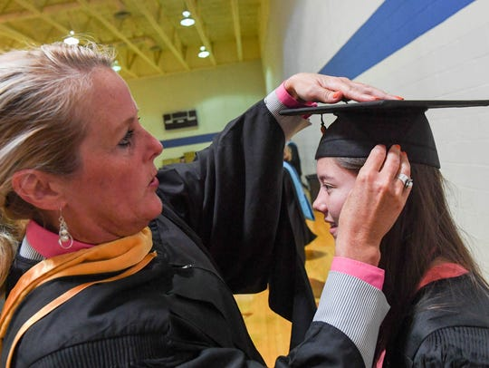 An Iowa teacher adjusts the graduation camp at a 2017 graduation ceremony.