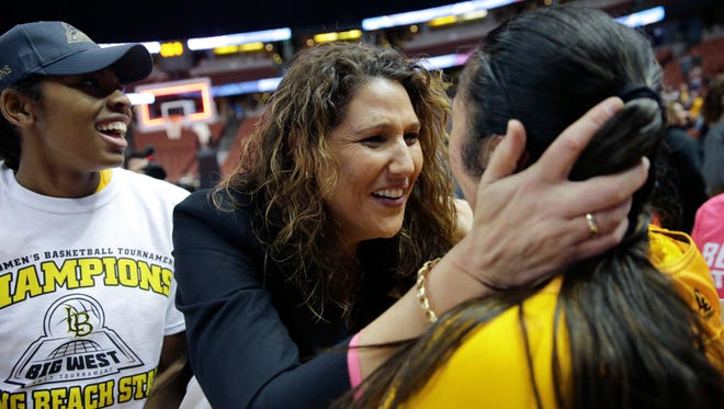 Long Beach State coach Jody Wynn (center) hugs one of her players after the 49ers  won the Big West Conference tournament last month to qualify for the NCAAs for the first time since 1992. Wynn accepted the Washington job on Friday.