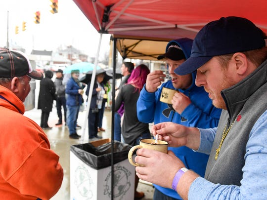Brent Couch (right) and Martin Deason enjoy warm mugs of gumbo at the Westside Nut Club booth during the Fourth Annual Gumbo Cook-Off held on West Franklin Street in Evansville Saturday. The event kicks off the Franklin Street Mardi Gras celebration next weekend, February 18, 2017.