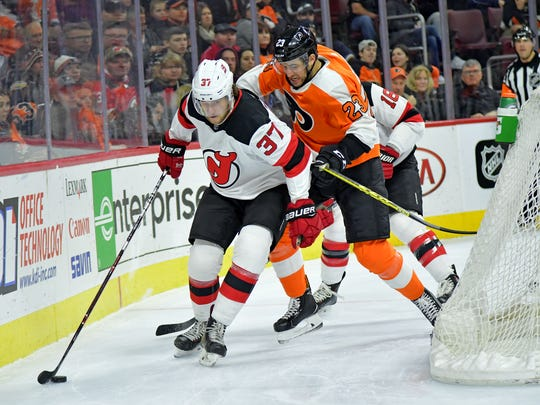 New Jersey Devils center Pavel Zacha (37) carries the puck against Philadelphia Flyers defenseman Brandon Manning (23) during the first period at Wells Fargo Center.