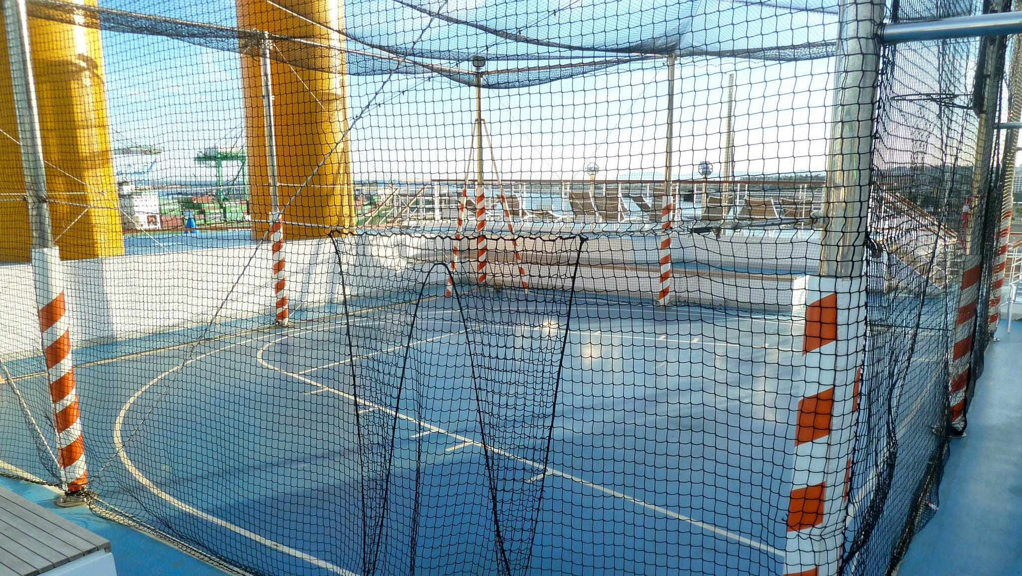 A net-covered games area on aft Fuxia Deck features a half basketball court.