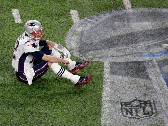 New England Patriots quarterback Tom Brady sits on
