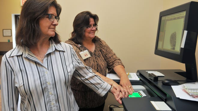 Pat Fleming and Sandy Rintelmann of the Brevard County Tax Collector's Office on Merritt Island train for the Wednesday start of concealed weapons permit licensing, working with the fingerprinting process.