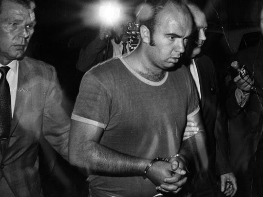 Raymond Kassow, 24, is led away by police in September 1969. He was one of three men who shot four women during a robbery at Cabinet Supreme Savings & Loan Association in Delhi Township.
