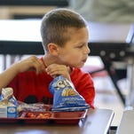 Cai McGillis, left, and his sister Aurora, share a moment as they eat a lunch at Paris Gibson Education Center.