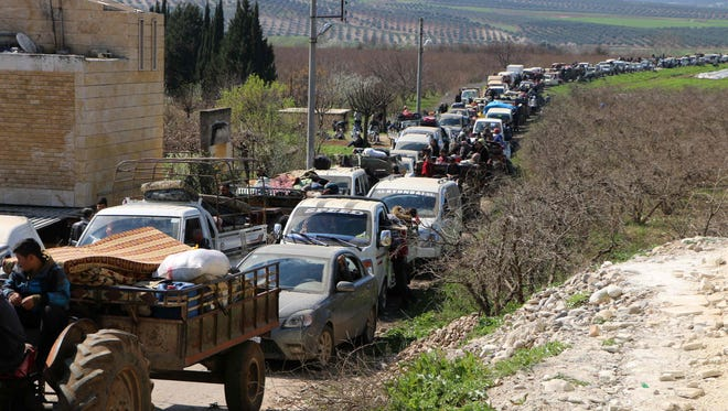 Syrian civilians ride their cars through Ain Dara in Syria's northern Afrin region as they flee Afrin city on March 12, 2018 amid battles between Turkish-backed forces and Kurdish fighters.