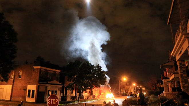 A police helicopter illuminates a burning car Wednesday, Aug. 19, 2015, after it was set ablaze following a fatal officer-involved shooting, in St. Louis. A black 18-year-old fleeing from officers serving a search warrant at a home in a crime-troubled section of St. Louis was fatally shot Wednesday by police after he pointed a gun at them, the city's police chief said. (Christian Gooden/St. Louis Post-Dispatch via AP) EDWARDSVILLE INTELLIGENCER OUT; THE ALTON TELEGRAPH OUT; MANDATORY CREDIT
