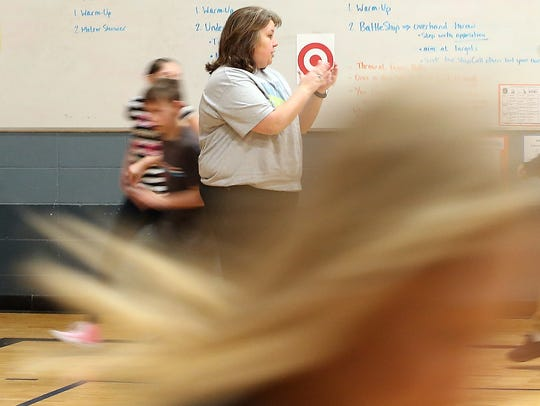 Sand Hill Elementary School's Shannon Dykman cheers on her students as they warm up by running a lap during PE class at Sand Hill Elementary in Belfair.