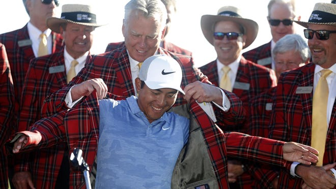 C.T. Pan puts on the traditional plaid jacket after winning the RBC Heritage golf tournament at Harbour Town Golf Links on Hilton Head Island, S.C.,  on April 21, 2019. Pan won with a 12-under par for his first PGA victory.