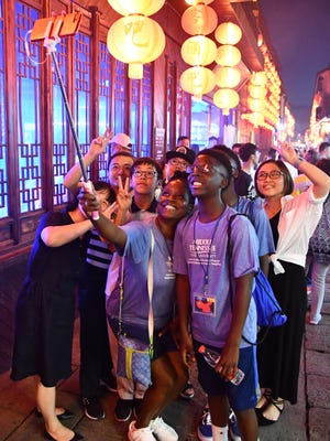 Parent Novonda Lilly takes a selfie with sons Chase (center) and Chandler, along with their Chinese hosts, in the ancient city of Xitang, China.