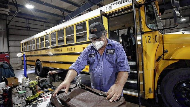 South-Western City Schools bus mechanic Dan Alkire reupholsters a bus seat July 9 in the district's transportation department. Workers are busy preparing the buses for the 2020-21 school year -- in whatever ways they are needed.