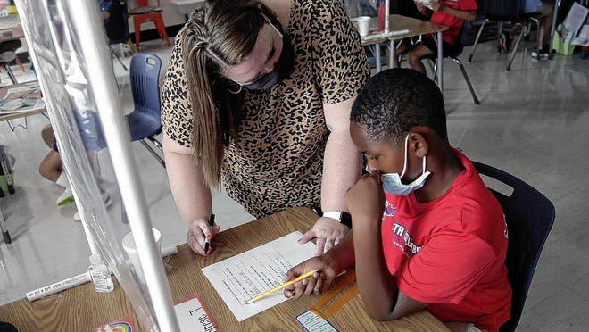 Fourth-grade teacher Emily Fulk helps Tyrese Travis, 9, of Columbus with an assignment Aug. 25 at South Columbus Prepatory Academy at German Village.