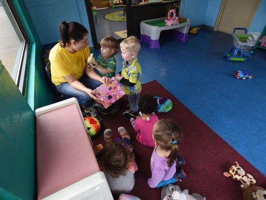Michelle McGee reads to a group of toddlers at the Little Barnyard Childcare Center in downtown Zanesville.