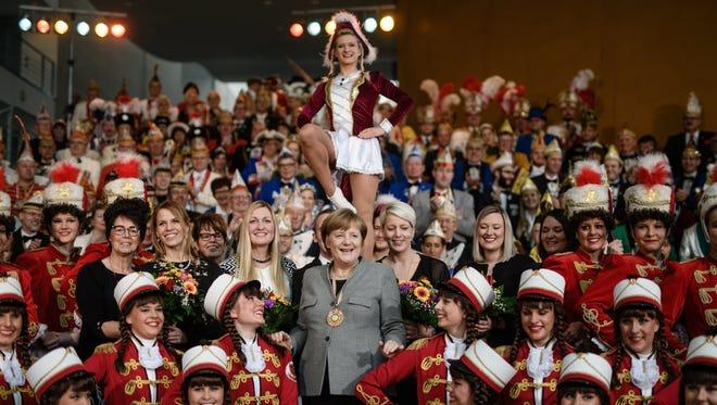 German Chancellor Angela Merkel poses with dancers of the 'Roten Husaren Neuenkirchen' in Berlin in January.