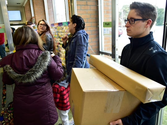 Steven Cooper, right, stands in a long line at the U.S. Post Office Chambersburg to mail Christmas gifts on Monday, December 19, 2016. Monday was considered the busiest mailing and shipping day for holiday packages.