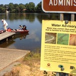 Bowers Beach resident Gary Boyle puts off from a dock in Silver Lake, Dover, for early afternoon bass fishing near a sign cautioning against contact with the water on days when blue-green algae blooms are dense.