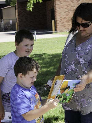 Megan Dotson and her sons Traven Dotson (back), 8, and Truett Dotson, 5, find two books from the Salina Area United Way Raising Active Wild Readers (RAWR) program  at Salina Central High School on Tuesday morning.
