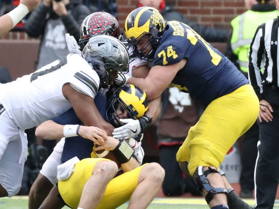 Michigan's John O'Korn is sacked by Ohio State's Michael