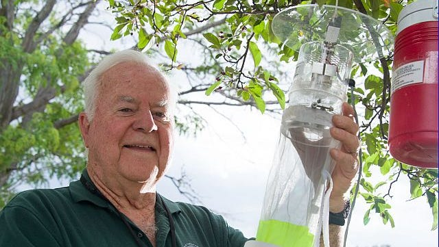 Colorado State University Microbiology, Immunology and Pathology professor Chester Moore hangs a mosquito trap used to track mosquito populations.