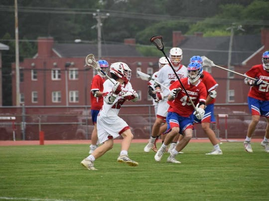 Midfielder Alex Sewell looks to pass during James M. Bennett's playoff lacrosse game against Centennial.