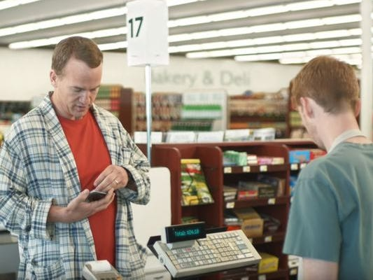 Peyton Manning, left, tries to find a coupon for an item he's buying in a DirecTV commercial. The grocery clerk, right, is Nashville native and Trevecca graduate James Austin Johnson.