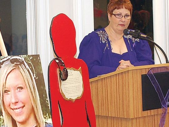 Kaye Chandler speaks at a domestic violence awareness event for Safe Haven Cheatham County. Pictured is a red silhouette of Courtney Price, a Middle Tennessee woman who lost her life to domestic violence.