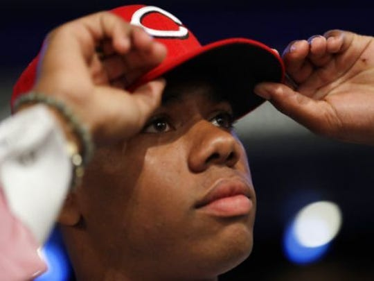 Hunter Greene puts on a Reds cap after being drafted